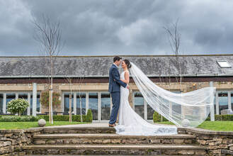 Couple hugging, outside The Yorkshire Wedding Barn, with brides veil blowing in the wind